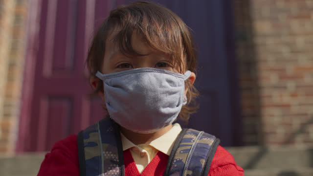 cu portrait of a boy sitting on doorstep of building as he puts on fabric protective face mask - schoolboy stock videos & royalty-free footage