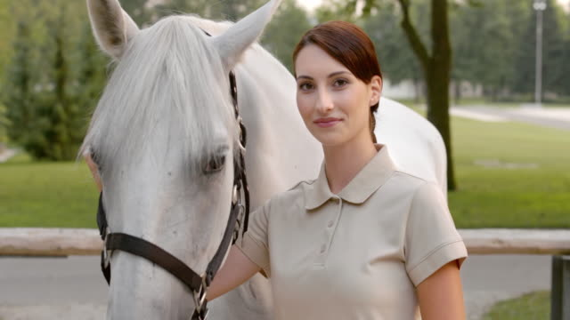 slo mo portrait of a brunette woman posing with her white horse - brown eyes stock videos and b-roll footage
