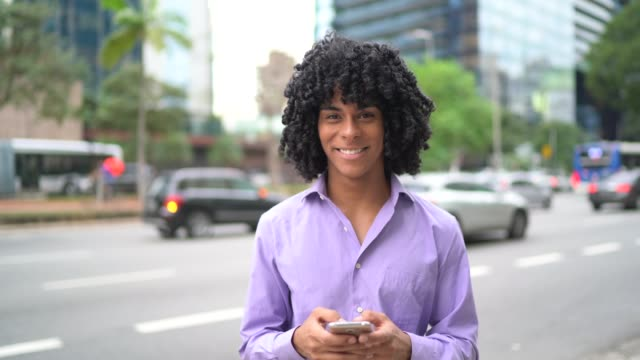 vídeos de stock, filmes e b-roll de retrato de um negócio ao ar livre usando o telemóvel - one young man only
