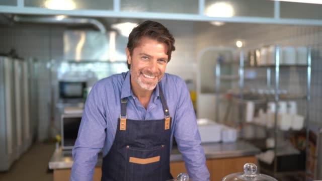 vídeos de stock e filmes b-roll de portrait of a business owner behind the counter at cafeteria - empregado de mesa