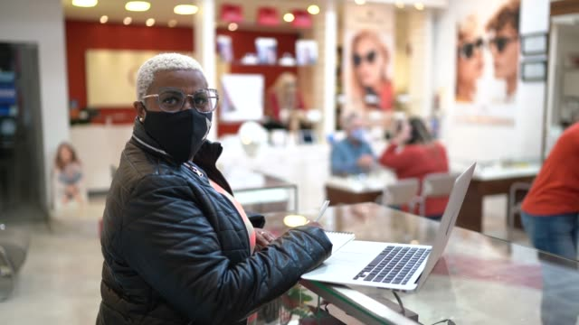 portrait of a business owner in an oprical store, wearng face mask and using laptop - opening event stock videos & royalty-free footage