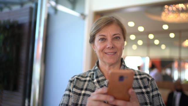 vídeos de stock, filmes e b-roll de retrato de uma mulher de negócio que usa o smartphone - área de embarque de aeroporto