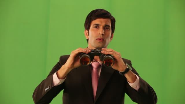 vidéos et rushes de portrait of a businessman looking through from a binoculars  - curiosité
