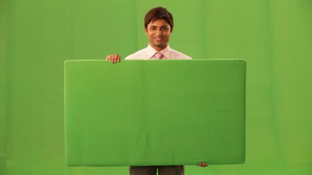 portrait of a businessman showing a placard  - 手に持つ点の映像素材/bロール