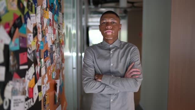vidéos et rushes de verticale d'un homme d'affaires restant avec des bras croisés à côté d'un panneau d'affichage plein de cartes de voeux - panneau d'information