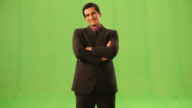 vidéos et rushes de portrait of a businessman standing with his arms crossed  - satisfaction