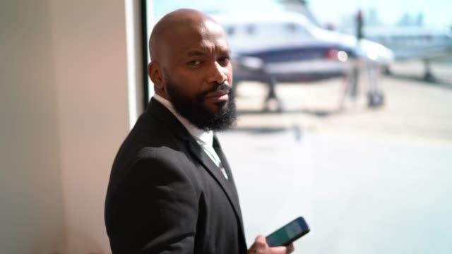 vídeos de stock, filmes e b-roll de retrato de um homem de negócios que usa o smartphone na frente de um indicador - área de embarque de aeroporto