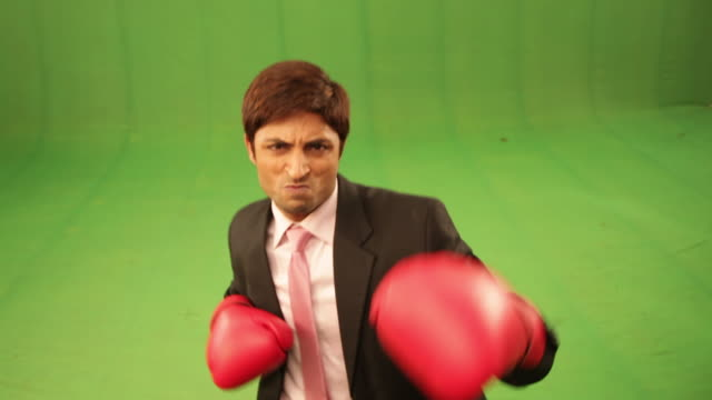portrait of a businessman wearing boxing gloves and punching  - faustschlag stock-videos und b-roll-filmmaterial