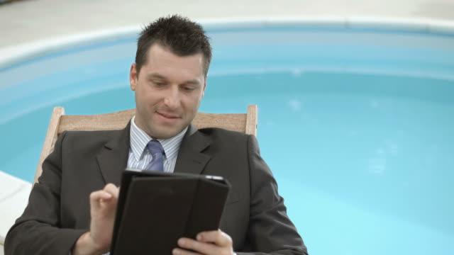vídeos de stock, filmes e b-roll de hd: retrato de um empresário com tablet - espreguiçadeira