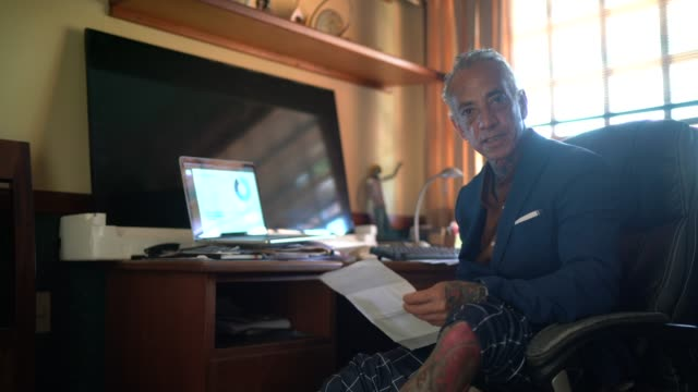 portrait of a businessman working from home wearing pajamas' pants while using laptop - tattoo stock videos & royalty-free footage