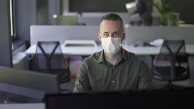 portrait of a businessman working in the office during a pandemic with a face mask - full suit stock videos & royalty-free footage