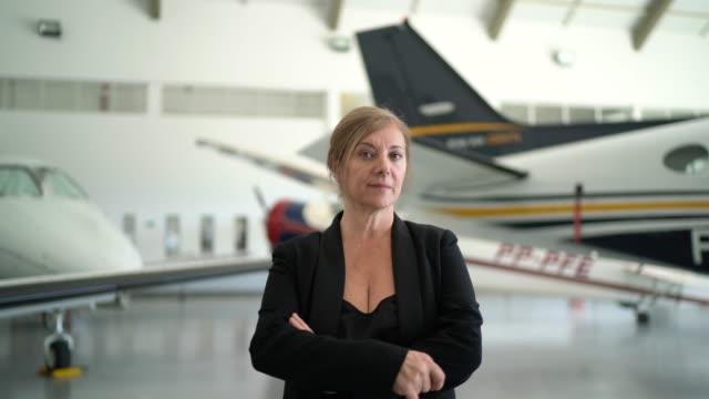 vídeos y material grabado en eventos de stock de retrato de una empresaria de pie en un hangar - juez derecho