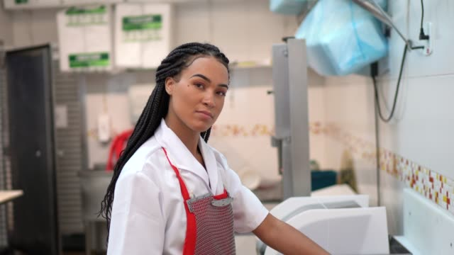 portrait of a butcher standing in a butcher's shop - young women stock videos & royalty-free footage