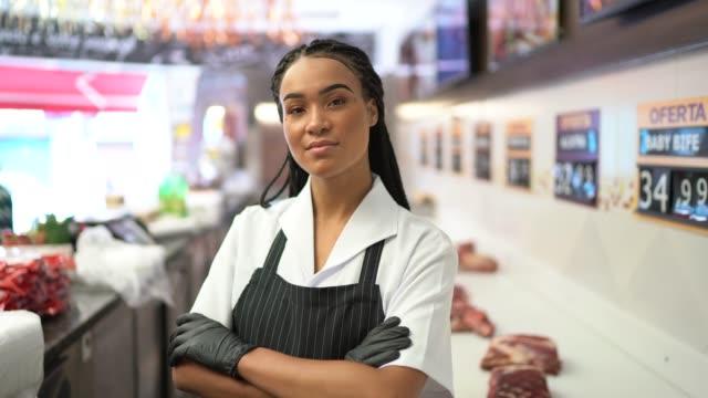 vídeos de stock, filmes e b-roll de retrato de um carniceiro que está com os braços cruzados em uma loja de carniceiro - vendendo