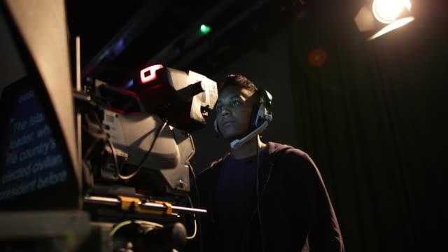 vídeos de stock, filmes e b-roll de portrait of a cameraman in a tv broadcasting studio - estúdio de televisão