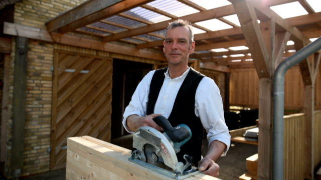 portrait of a carpenter at work with the portable circular saw - work tool stock videos & royalty-free footage
