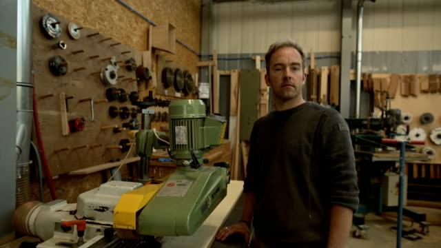 Portrait of a carpenter on a wide belt sander in a carpentry