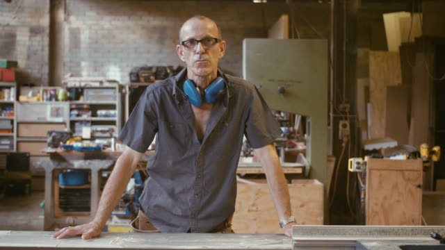 portrait of a carpenter (slow motion) - ear protectors stock videos and b-roll footage