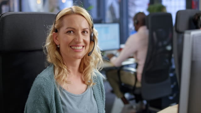 portrait of a caucasian female call center agent smiling into the camera at her office desk - blonde hair stock videos & royalty-free footage