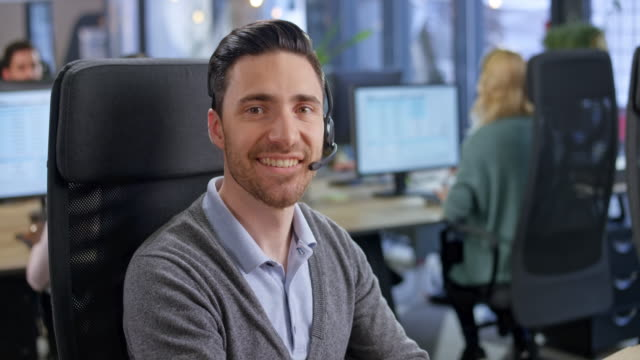 portrait of a caucasian male call center agent smiling while sitting at his desk in the call center offices - telecommunications worker stock videos & royalty-free footage