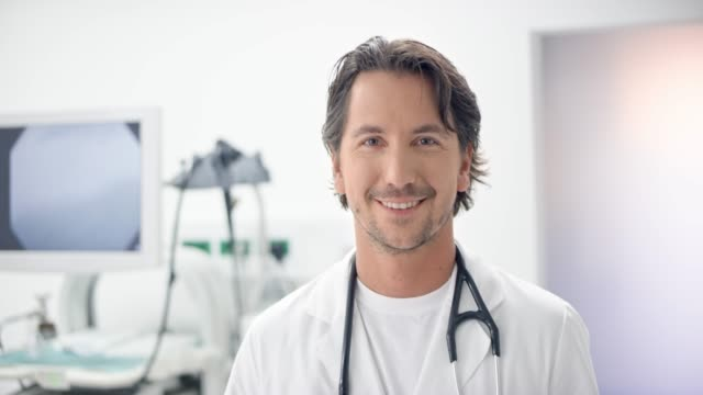 portrait of a caucasian male doctor using a digital tablet in his office and smiling into the camera - part of a series stock videos & royalty-free footage