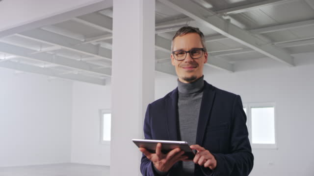 portrait of a caucasian male interior architect holding a digital tablet and smiling while standing in an empty business building - approaching stock videos & royalty-free footage