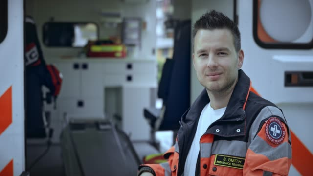 portrait of a caucasian male paramedic standing by the stretcher - paramedic stock videos & royalty-free footage