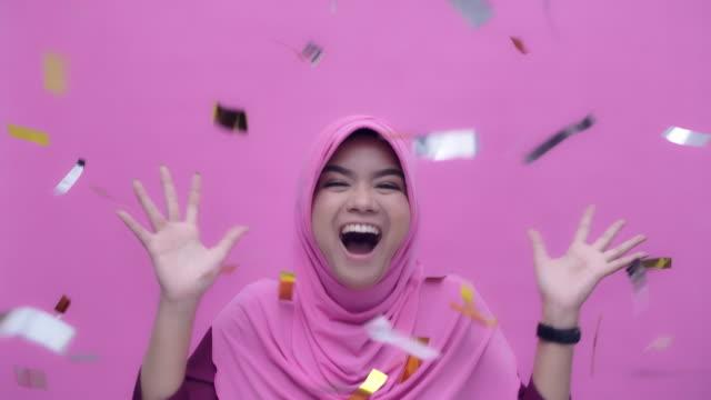 vídeos de stock, filmes e b-roll de retrato do mo de slo de uma mulher nova atrativa muçulmana cheeful que comemora o partido no confetti de queda, movimento lento - fundo rosa