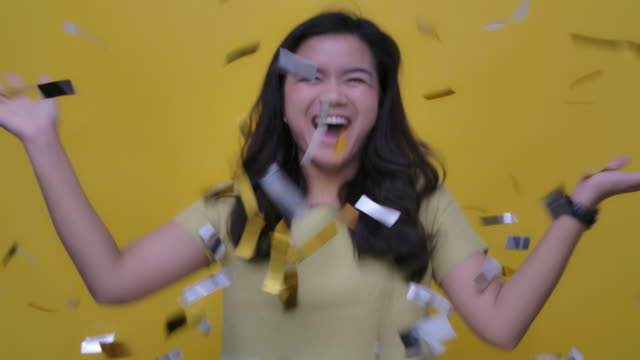 slo mo portrait of a cheerful attractive young asian woman celebrating party in falling gold confetti studio shot on yellow background, slow motion - sequin stock videos & royalty-free footage