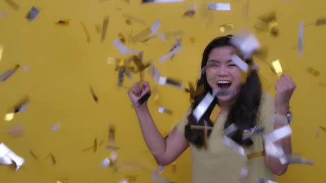 立ち下がり金紙吹雪でパーティーを祝う陽気で魅力的な若いアジアの女性のスローモーションの写真黄色の背景、スローモーション - バナー看板点の映像素材/bロール