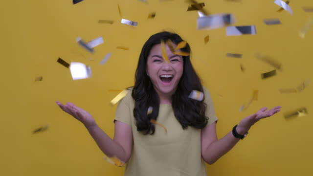 stockvideo's en b-roll-footage met slo mo portret van een vrolijke aantrekkelijke jonge aziatische vrouw vieren partij in vallende goud confetti studio geschoten op gele achtergrond, slow motion - studio shot