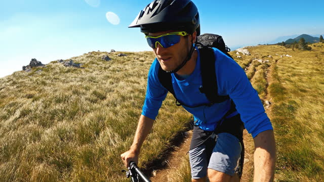portrait of a cheerful mountain biker cycling on dirt road in grass covered mountains - recreational horse riding stock videos & royalty-free footage