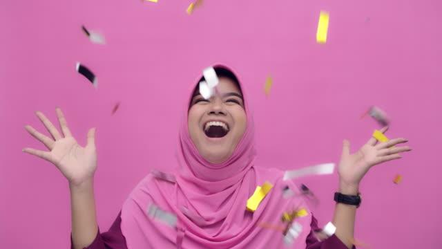 vídeos de stock, filmes e b-roll de retrato do mo de slo de uma mulher nova atrativa muçulmana alegre que comemora o partido no confetti de queda, movimento lento - fundo rosa