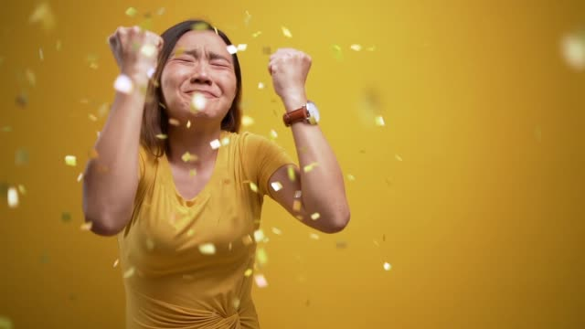portrait of a cheerful woman with confetti rain and celebrating over isolated yellow background - coloured background stock videos & royalty-free footage