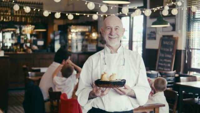 アルゼンチンのレストランでエンパナダを持つシェフの肖像 - アシスタント点の映像素材/bロール