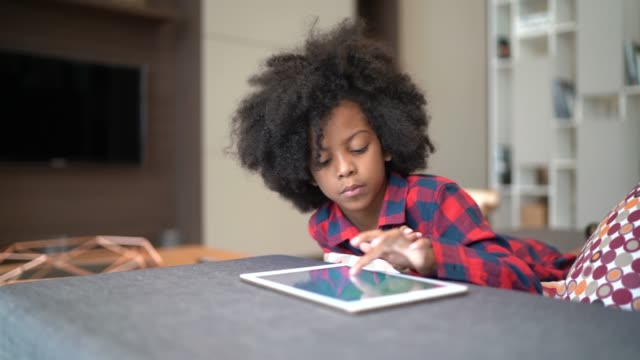 portrait of a child playing with digital tablet at home - afro stock videos & royalty-free footage