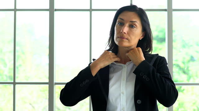 portrait of a confident businesswoman standing and adjusting her suit.close-up of young businesswoman adjusting her jacket. - suit jacket stock videos & royalty-free footage