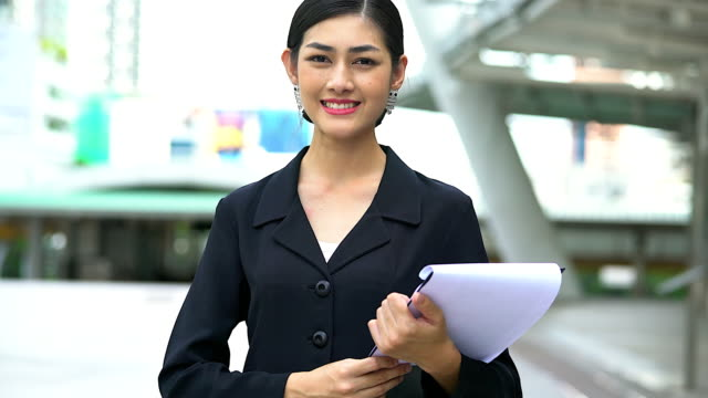 portrait of a confident businesswoman standing on the footpath.close-up of a young businesswoman holding the document. - collar stock videos and b-roll footage