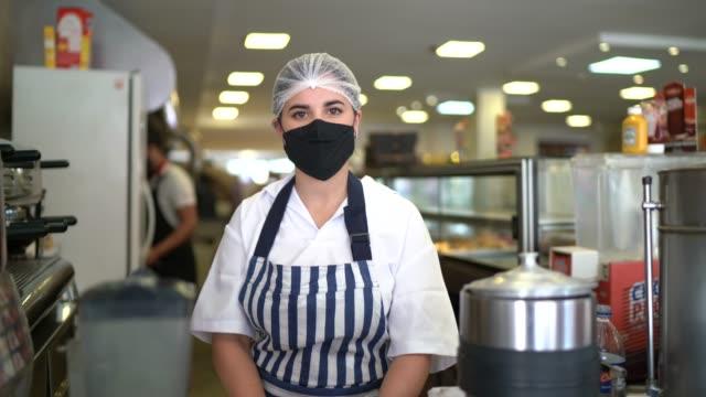 vídeos de stock, filmes e b-roll de retrato de um funcionário confiante em uma cafeteria com máscara facial - funcionário