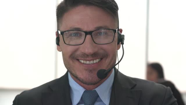 vídeos y material grabado en eventos de stock de retrato de un representante de llamadas masculina sin confianza con auriculares mirando la cámara - soporte informático