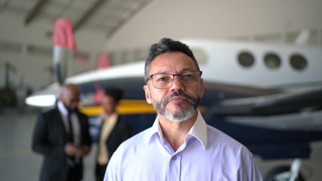 vídeos y material grabado en eventos de stock de retrato de un hombre confiado en un hangar - presidente de organización