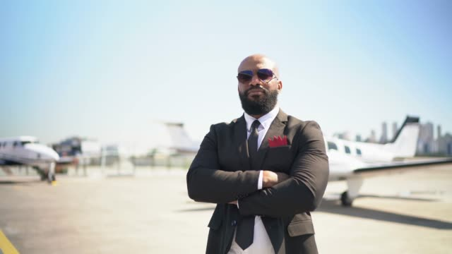 vídeos de stock, filmes e b-roll de retrato de um homem confiável que olha a câmera em um hangar - braços cruzados