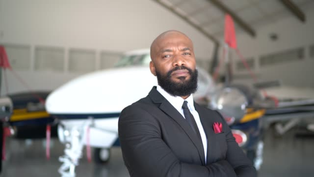 portrait of a confident man looking at camera in a hangar - airplane hangar stock videos & royalty-free footage