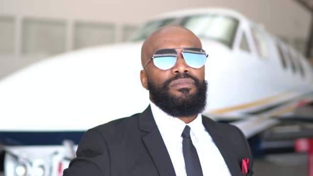 portrait of a confident man looking at camera in a hangar - sunglasses stock videos & royalty-free footage