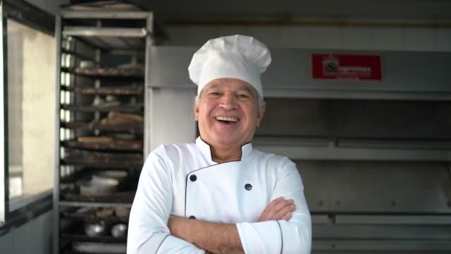 porträt eines selbstbewussten seniorbäckers, der in einer großküche mit gekreuzten armen steht - stolz stock-videos und b-roll-filmmaterial