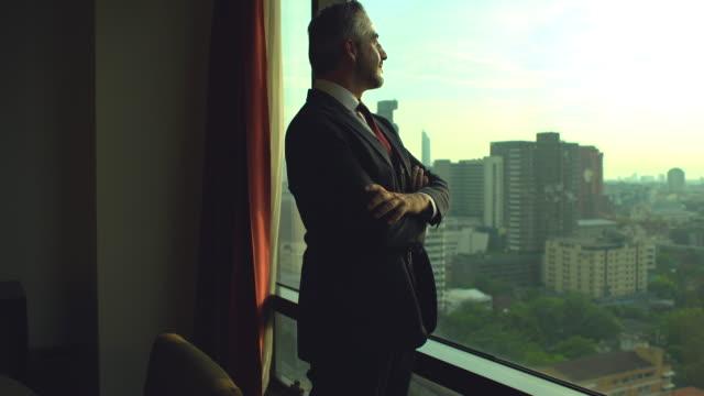 オフィスルームの窓の近くに立っている自信に満ちた先輩ビジネスマンの肖像画。 - 男性のみ点の映像素材/bロール