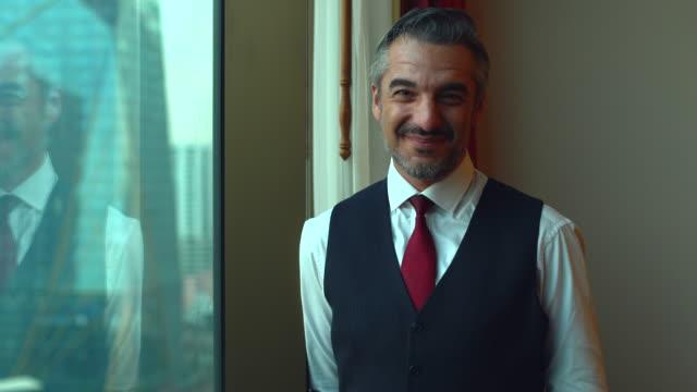 portrait of a confident senior businessman standing near the window in his office room. - handsome people stock videos & royalty-free footage