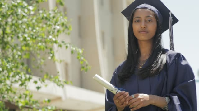 portrait of a confident young indian woman wearing her high school graduation mortarboard and gown holding her diploma - mortar board stock videos & royalty-free footage
