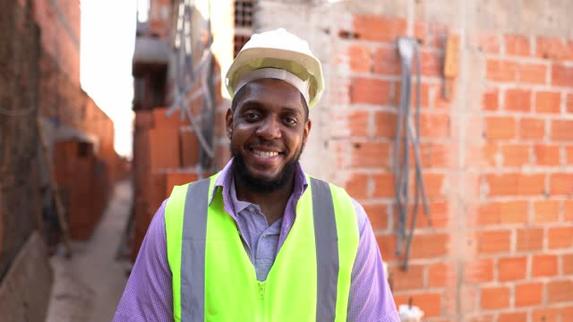 stockvideo's en b-roll-footage met portrait of a construction worker at a construction site - hoofddeksel