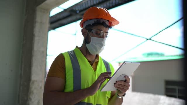 建設現場で働くデジタルタブレットを持つ建設労働者の肖像画 - 保護フェイスマスクを着用 - 土木技師点の映像素材/bロール